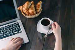 篮子用鲜美新鲜的新月形面包和热的早晨咖啡 免版税库存图片