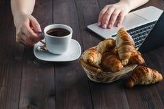 篮子用鲜美新鲜的新月形面包和热的早晨咖啡 免版税图库摄影