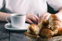 篮子用鲜美新鲜的新月形面包和热的早晨咖啡 免版税库存照片