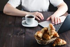 篮子用鲜美新鲜的新月形面包和热的早晨咖啡 图库摄影