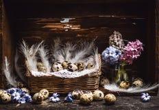 篮子用鹌鹑蛋和羽毛和春天开花在葡萄酒木桌上的风信花束,在土气背景,侧视图 库存照片
