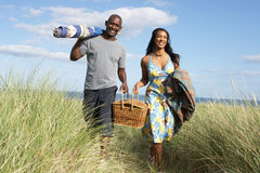 篮子运载的夫妇野餐throug走 免版税库存图片