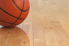 篮球低角度视图在木健身房地板上的 免版税库存照片