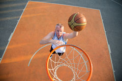 篮球做灌篮的街道球员 库存图片