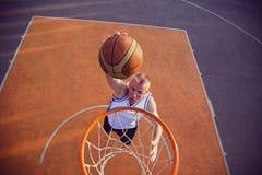 篮球做灌篮的街道球员 库存照片