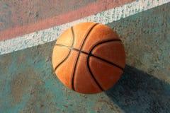 篮球和阴影在地面上在微明下 免版税图库摄影