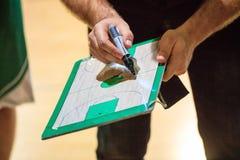 篮球教练拿着一张剪贴板,并且与标志解释比赛的战术给球员 图库摄影
