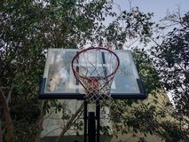 篮球结构外缘在树包围的一个室外操场在公园 库存图片