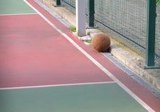 篮球,室外篮球场的被忘记的运动员在锻炼以后 免版税库存照片