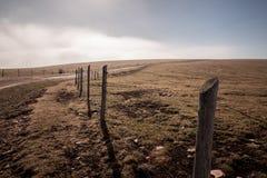 篱芭和路在一座山顶部,与低云在ho 免版税图库摄影