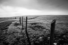 篱芭和路在一座山顶部,与低云在ho 库存图片