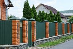 篱芭和门由金属和砖做成在街道在路附近 库存图片