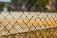 篱芭在有被弄脏的农村橄榄球场的滤锅设计的由架线的钢制成在背景中 免版税库存照片