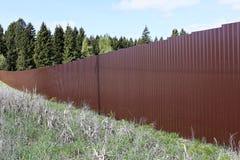 篱芭由棕色金属专业地板制成 免版税库存图片