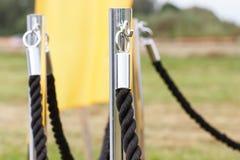 篱芭由绳索和镀铬物杆制成作为事件的保护 免版税库存图片
