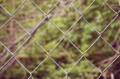 篱芭由金属滤网特写镜头制成 在篱芭后是干草 抽象背景 库存图片