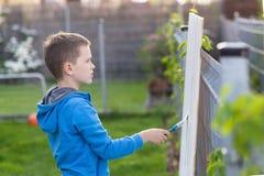 绘篱芭的小男孩孩子在庭院里 免版税库存图片