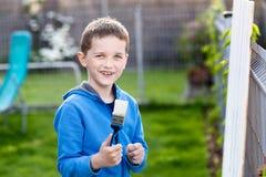 绘篱芭的小男孩孩子在庭院里 免版税库存照片