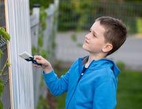 绘篱芭的小男孩孩子在庭院里 库存图片