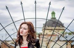篱芭的背景和一个寺庙的圆顶的年轻美丽的女孩在老市的步行小街道的期间利沃夫州 免版税库存照片