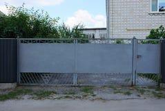 篱芭的长的灰色闭合的金属门和零件 免版税库存照片