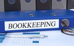 簿记-与文本的蓝色黏合剂在办公室 库存图片