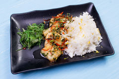 米、油煎的菜和鱼 在一张木桌上的完成的盘 图库摄影