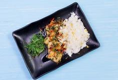 米、油煎的菜和鱼 在一张木桌上的完成的盘 库存照片