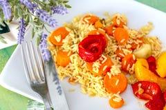 米、红萝卜和红色黄色油煎的甜椒在一块白色陶瓷板材在一张木桌上 免版税库存图片