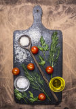 米、西红柿、迷迭香和草本,木匙子,在一个切板的香料在木土气背景顶视图关闭 免版税库存照片