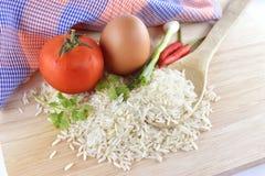 米、辣椒、葱、鸡蛋和蕃茄在木背景 免版税库存图片