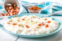 米与坚果和葡萄干的牛奶粥在一张白色木桌上的一个蓝色盘 免版税库存图片