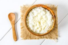 米与坚果和葡萄干的牛奶粥在一张白色木桌上的木碗 库存照片