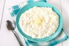 米与坚果和葡萄干的牛奶粥在whi的一个蓝色盘 免版税库存照片