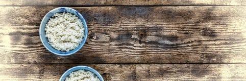 米传统地道印地安和亚洲食物 在两个蓝色碗的米在木钢在餐馆 免版税库存图片