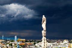 米兰大教堂圆顶的雕象有在雷前的城市视图 图库摄影