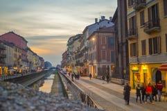 米兰意大利Navigli运河的日落视图有颜色三张相同和二张相同的牌和人走的 库存照片