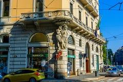 米兰,意大利- 2015年10月19日, :与雕塑造型男人和妇女的老药房大厦在壁角街道Filippo Turati上 免版税库存图片