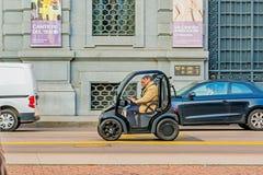 米兰,意大利- 2015年10月19日, :两乘驾的微型电车在米兰街道上在意大利 在一个人的轮子后a的 库存图片