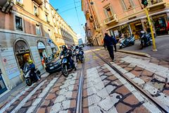 米兰,意大利- 2015年10月19日, :站立在街道上的摩托车骑士和汽车等待绿色红绿灯发信号 免版税库存图片