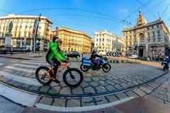 米兰,意大利- 2015年10月19日, :年长骑自行车者和一位警察一辆摩托车的在路在城市街道通过Cordusio米拉 库存图片