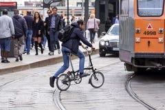 米兰,意大利- 2018年5月04日:使用一辆折叠的自行车,一个人参观城市 这交通工具是舒适快速的和 库存照片