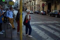 米兰,意大利- 2017年10月8日:米兰,一条行人交叉路的人们晚上街道  免版税库存照片
