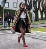 米兰- 2018年2月25日:摆在为街道的摄影师的时髦的女人在阿玛尼时装表演前,在米兰Fashi期间 免版税库存图片
