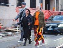 米兰-1月13日:走在街道的两个时髦的女人在尼尔毛尼雨衣时装表演以后,在米兰时尚星期秋天/胜利期间 免版税库存图片