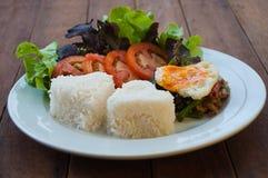 米冠上了用混乱油煎的猪肉和蓬蒿用鸡蛋 免版税库存图片