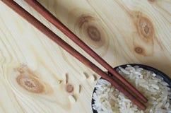 米和筷子在木桌上 库存照片
