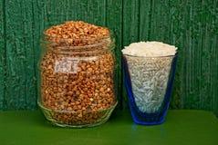 米和荞麦在玻璃和瓶子 免版税库存图片