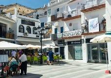 米哈斯, ANDALUSIA/SPAIN - 9月11日:米哈斯-典型的白色镇街道有小餐馆的在安大路西亚,南西班牙, p 免版税图库摄影