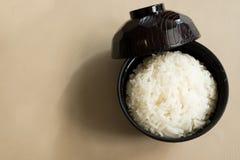 米在一个黑木杯子的碳水化合物上是浓的煮熟的茉莉花在桌被安置并且准备对担当早餐 免版税库存照片